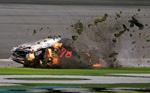 Горящий автомобиль пилота Мартина Труэ-младшего во время этапа серии NASCAR Sprint Cup series qualifying на трассе в Дайтоне Бич