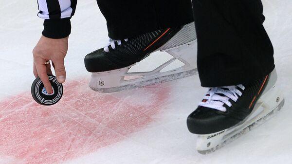 шайба Континентальной хоккейной лиги в руках арбитра