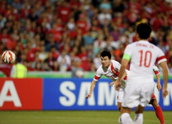 Нападающий сборной Китая Сун Ке забивает мяч в ворота сборной КНДР