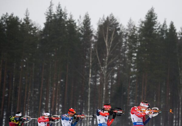 Биатлонисты Мартен Фуркад (Франция), Тарьей Бё (Норвегия), Антон Шипулин (Россия) (слева направо) на огневом рубеже гонки. преследования