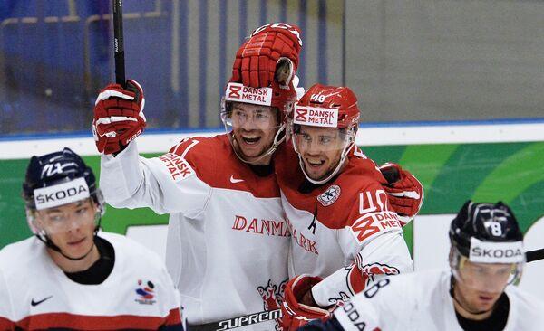 Хоккеисты сборной Дании Патрик Бьоркстранд и Йеспер Йенсен (в центре слева направо) радуются заброшенной шайбе