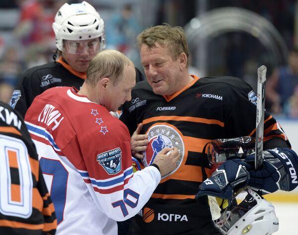 Президент России Владимир Путин расписывается на форме участника после окончания гала-матча турнира Ночной хоккейной лиги в Сочи