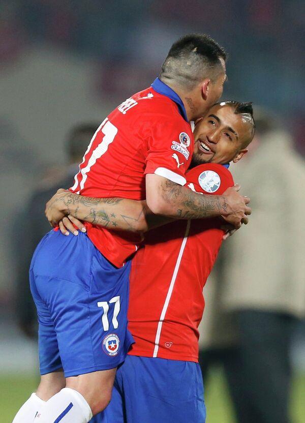Игроки сборной Чили по футболу Гари Медель и Артуро Видаль (слева направо) радуются забитому голу