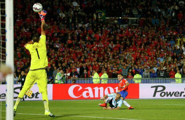 Нападающий сборной Чили Алексис Санчес (на дальнем плане) пытается перекинуть голкипера сборной Аргентины Серхио Ромеро