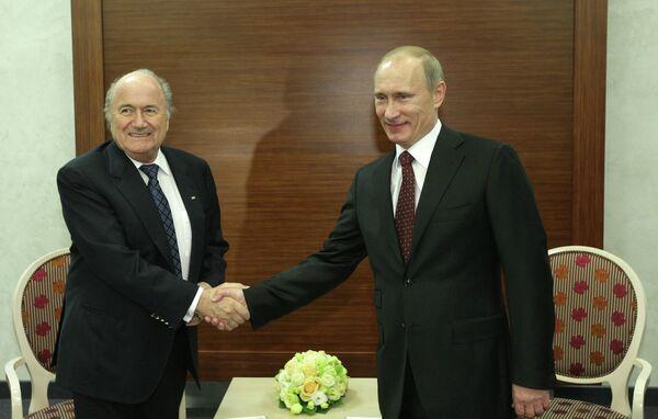 Президент РФ Владимир Путин (справа) беседует с президентом ФИФА Йозефом Блаттером (слева)