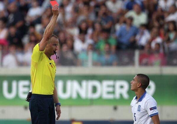 Арбитр показывает красную карточку защитнику юношеской сборной Греции Тимосу Целепидису