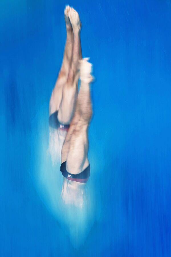 Спортсмены на разминке перед соревнованиями по синхронным прыжкам в воду с вышки 10 м среди мужчин