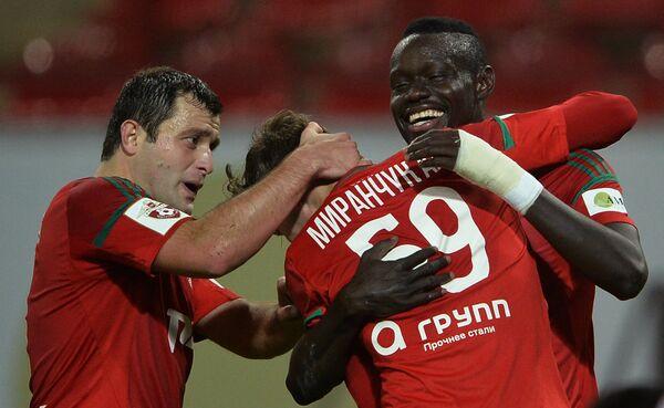 Игроки Локомотива Алан Касаев, Алексей Миранчук (автор гола) и Байе Умар Ниассе (слева направо) радуются забитому голу