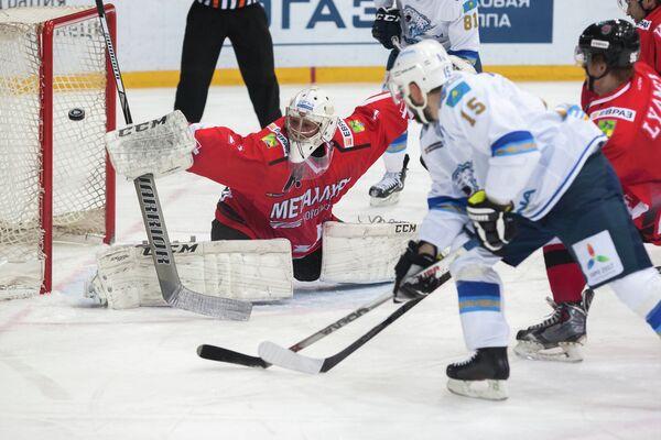 Голкипер ХК Металлург (Новокузнецк) Андрей Кареев и форвард Барыса Максим Худяков (справа)