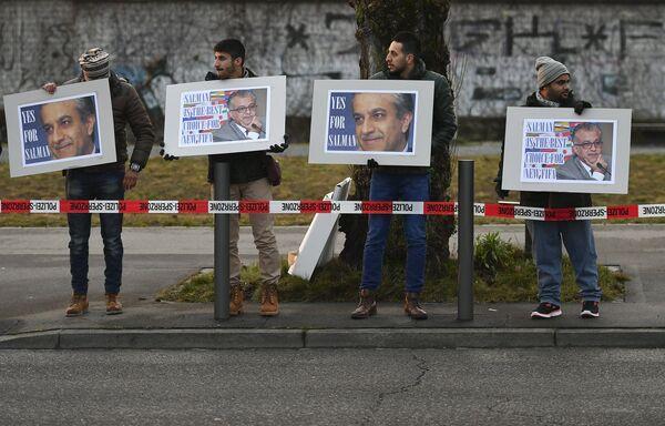 Люди с плакатами поддерживают шейха Салмана у штаб-квартиры ФИФА