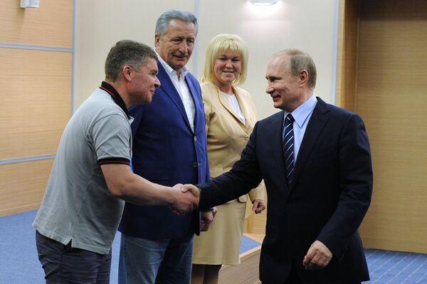Президент России Владимир Путин (справа) во время встречи с победителями V Всероссийского фестиваля по хоккею среди любительских команд