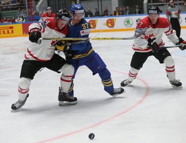 Защитник сборной Канады Морган Райлли (слева) и форвард сборной Швеции Джон Норман (в центре)