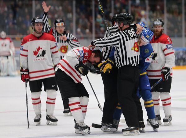 Потасовка между форвардом сборной Канады Брэдом Маршаном (в центре) и нападающим шведской сборной Юханом Сундстрёмом (справа)