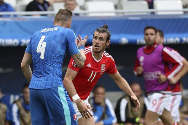 Защитник сборной Словакии Ян Дюрица и нападающий сборной Уэльса Гарет Бэйл (справа)
