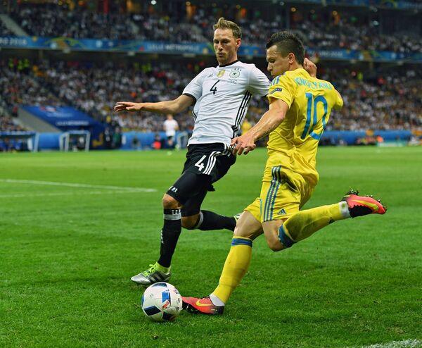 Полузащитник сборной Украины Евгений Коноплянка (справа) и защитник сборной Германии Бенедикт Хёведес