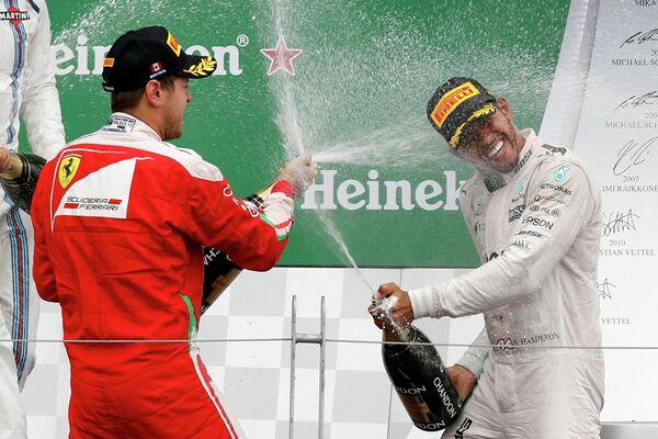 Гонщик команды Феррари Себастьян Феттель (слева) и гонщик команды Мерседес Льюис Хэмилтон