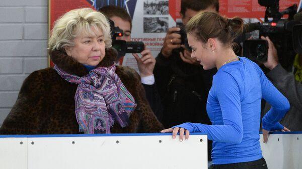 Российская фигуристка Аделина Сотникова (в центре) и тренер Татьяна Тарасова (слева) на тренировке