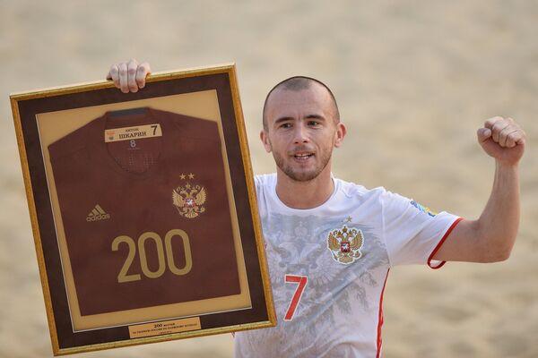 Защитник сборной России Антон Шкарин держит в руках памятную футболку