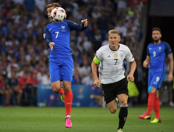 Нападающий сборной Франции Антуан Гризманн (слева) и полузащитник сборной Германии Бастиан Швайнштайгер